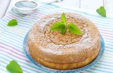 Japanese cheesecake decorated with mint, icing sugar and strawberry
